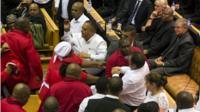 Members of Julius Malema's Economic Freedom Fighters (EFF) (in red) clash with security officials after being ordered out of the chamber during President Jacob Zuma's State of the Nation address in Cape Town on 12 February 2015