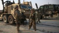 US and British soldiers chat at the site of a suicide attack in Kabul, Afghanistan