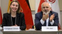 EU's foreign policy chief Federica Mogherini (L) and Iranian Foreign Minister Mohammad Javad Zarif smile ahead of the opening of a plenary session on Iran nuclear talks at the Beau Rivage Palace Hotel in Lausanne, Switzerland, on 30 March 2015