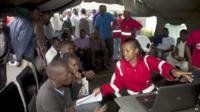 Red Cross workers at Nairobi funeral home help relatives check list of survivors - 4 April