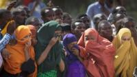 People in Garissa watch as the bodies of the dead gunmen are driven past - 4 April