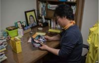In a photo taken on 11 April 2015 Lee Keum-Hui looks at photos in the bedroom of her daughter Cho Eun-Hwa, a victim of the Sewol ferry disaster who remains unaccounted for, in Ansan