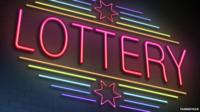 Lottery sign lights up in neon