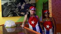 Waitresses at a Havana cafeteria, with a poster of Fidel Castro