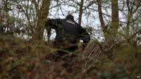 Police officer searching undergrowth