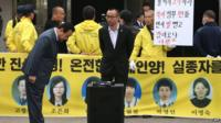 South Korean Prime Minister Lee Wan-Koo (L) bows as he is blocked by family members of the victims of the sunken South Korean ferry Sewol outside a remembrance hall in Ansan on 16 April 2015
