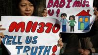 Catherine Gang, whose husband Li Zhi was on board the missing Malaysia Airlines flight MH370, holds a sign during a gathering of family members of the missing passengers outside the Malaysian embassy in Beijing, China, 8 March 2015