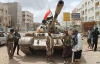 Yemeni members of the separatist Southern Movement stand beside a tank in Aden (15 April 2015)