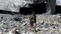 A Houthi rebel walks among the ruins of a stadium allegedly destroyed by a Saudi air strike in Sanaa, Yemen (12 April 2015)