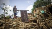 An elderly man stands on the ruins of his home in Paslang village in Gorkha, Nepal, on 20 April