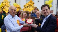 Nick Clegg and Vince Cable hold a cake after the Lib Dem leader's visit to Mr Cable's Twickenham constituency