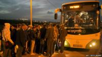 Palestinians queue to board a bus as a new line is made available by Israel to take Palestinian labourers from the Israeli army crossing Eyal, near the West Bank town of Qalqilya, into the Israeli city Tel Aviv, 4 March 2013