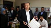 Turkey's President Recep Tayyip Erdogan, accompanied by his wife Emine, left, holds his ballot as he prepares to vote at a polling station in Istanbul.