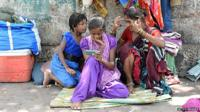 Lady watching video on her smartphone on a pavement in India