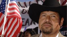 Juan Galvan holds a U.S. flag as he participates in the Mega March on City Hall April 9, 2006 in Dallas, Texas
