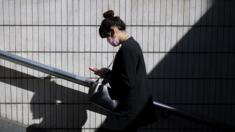 A woman walks as she reads her text on her phone in Beijing, on 23 March 2016.