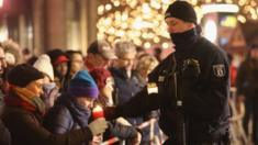 A policeman takes a candle from a mourner to place it at a makeshift memorial in Berlin