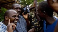 kenyan men listen to radio