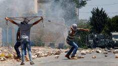 A Palestinian protester uses a slingshot to hurl stones towards Israeli security forces during clashes following a weekly demonstration against the expropriation of Palestinian land by Israel on 1 July