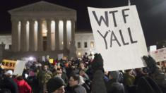 The US Supreme Court, seen in the background, is obstructed by a protesters's sign reading
