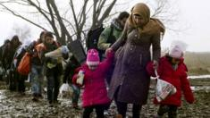 Migrants walk through thick mud as they cross the Macedonia-Serbia border in the southern Serbia (27 January 2016)