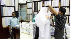 A salesman helps a customer as he tries on a traditional headdress and dishdasha (robe) at a shop in Dubai late September 28, 2008