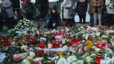 Mourners lay flowers and candles at a makeshift memorial near the site where a man drove a heavy truck into a Christmas market in an apparent terrorist attack