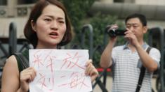 Li Wenzu, wife of imprisoned lawyer Wang Quanzhang, holds a paper that reads