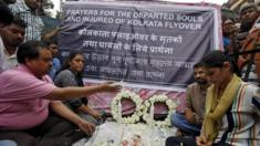 People hold a memorial service at the site of the collapsed flyover in Kolkata