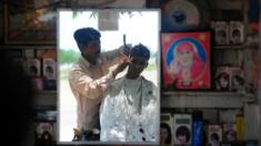 An Indian barber attends to a customer at his roadside hairdresser shop in Allahabad on July 6, 2013.