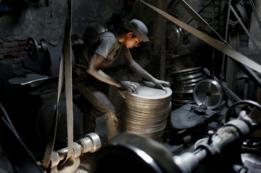 Un chico trabaja en una empresa de utensilios de aluminio en Daca, la capital de Bangladés.