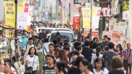 Gente caminando en calle comercial en Seúl, Corea del Sur.
