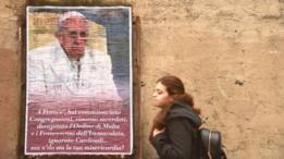 Una joven pasa por el lado de un cartel del Papa