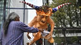 متظاهر يشعل النار في تمثال لترامب وعلى رأسه علم امريكا