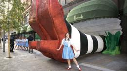 Mujer vestida como Dorothy posa frente a un modelo gigante de los zapatos rojos al lado de la tienda Harrods.