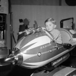 Un niño juega en una atracción que simula una nave espacial en 1968 en Londres.