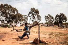 Un manifestante usa una honda para disparar una piedra a la policía anti-disturbios.