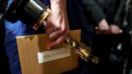Un Oscar y un sobre con el nombre del ganador.
