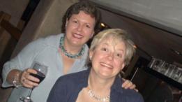 Mujer con a copa de vino en la mano junto a su hermana
