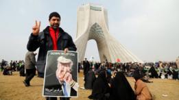 متظاهر يحمل صورة كاريكاتورية لترامب يتلقى ضربة من إيران