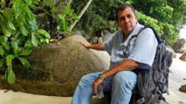 John sentado frente a una roca con unas marcas