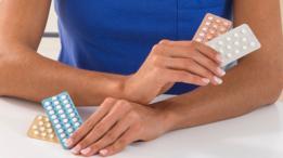 Manos de mujer con pastillas anticonceptivas.