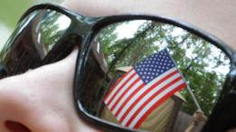 Una bandera estadounidense reflejada en unos lentes de sol