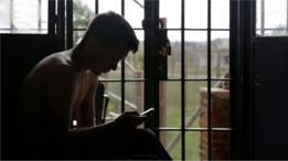 Un recluso usa su celular en Punta de Rieles