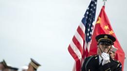 Guardia militar estadounidense lleva una bandera de su país y otro lleva una bandera china.