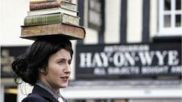 Una mujer con libros sobre su cabeza frente a un letrero de Hay-on-Wye