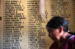Mujer ante un cartel que recuerda a las víctimas de la masacre en Plan de Sánchez, Baja Verapaz, Guatemala.