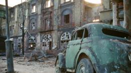 Un automóvil abandonado frente a una edificación derruida