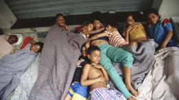 Niños de la calle durmiendo juntos. Una adolescente abraza a dos niños pequeños.