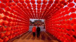 Dos personas cruzan por un túnel de lámparas rojas